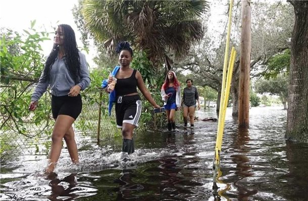 "Vier junge Frauen waten durch das Hochwasser nach starken Regenfällen ausgelöst von Tropensturm ""Eta"" nördlich des Broward Boulevards in Florida. Foto: Joe Cavaretta/TNS via ZUMA Wire/dpa"